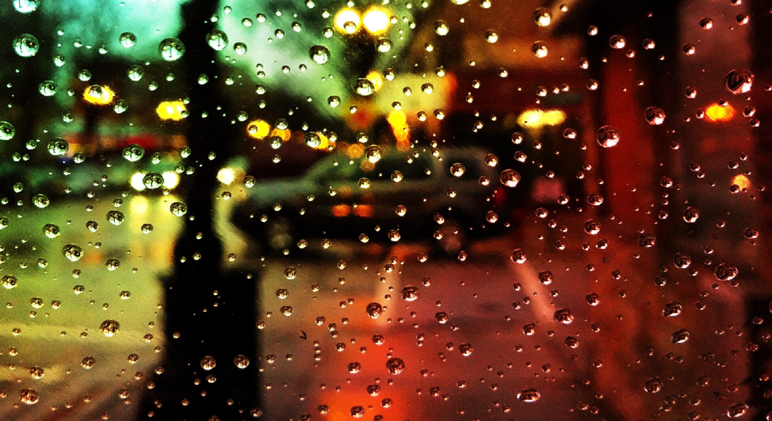partial view of lamppost and street through raindropped glass