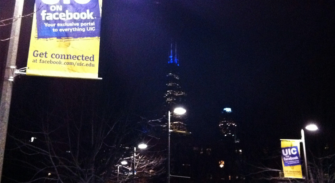 nighttime shot of chicago Willis tower with UIC banners