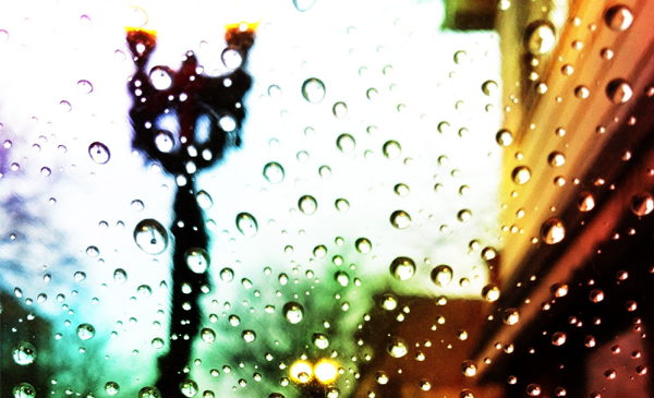 close up of a lamp post through raindropped glass